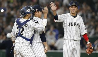 Japan's Hayato Sakamoto, right, celebrates with catcher Seiji Kobayashi and closer Kazuhisa Makita, center, after beating Cuba 11-6 in their first round game of the World Baseball Classic at Tokyo Dome in Tokyo, Tuesday, March 7, 2017. (AP Photo/Shizuo Kambayashi)