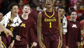FILE - In this Feb. 22, 2017, file photo, Minnesota guard Dupree McBrayer (1) reacts in front of teammates after making a 3-pointer during the second half of the team's NCAA college basketball game against Maryland in College Park, Md. McBrayer and Nate Mason were suspended last year at the end of a miserable season for their connection to a sex video that briefly was posted on social media. The two friends decided to stay at Minnesota, and they have both been integral parts of a team that has enjoyed one of the biggest single-season turnarounds in the country this season.  (AP Photo/Patrick Semansky, File)