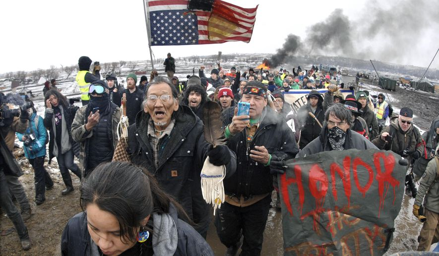 In this  Feb. 22, 2017, file photo, a large crowd representing a majority of the remaining Dakota Access Pipeline protesters march out of the Oceti Sakowin camp before the 2 p.m. local time deadline set for evacuation of the camp mandated by the U.S. Army Corps of Engineers near Cannon Ball, N.D. (Mike McCleary/The Bismarck Tribune via AP, File)