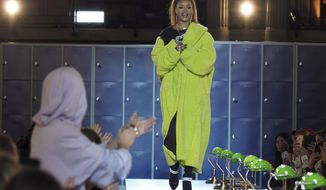 Singer and fashion designer Rihanna acknowledges applause at the end of her Fall-Winter 2017/2018 ready-to-wear collection for Fenty as part of Paris Fashion Week, presented in Paris, Monday March 6, 2017. (AP Photo/Thibault Camus)