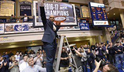 Mount St. Mary's head coach Jamion Christian cuts down a net after his team beat St. Francis (Pa.) 71-61 in the NCAA college basketball Northeast Conference Tournament championship, Tuesday, March 7, 2017, in Emmitsburg, Md. (AP Photo/Steve Ruark)