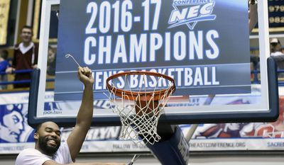 Mount St. Mary's guard Charles Glover cuts down a net after his team beat St. Francis (Pa.) 71-61 in the NCAA college basketball Northeast Conference Tournament championship, Tuesday, March 7, 2017, in Emmitsburg, Md. (AP Photo/Steve Ruark)
