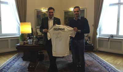 In this photo provided by the Office of the Slovenia's president and used on president's Instagram, Slovenia's president Borut Pahor, left, holds a T-shirt signed by famous coach Jose Mourinho, given to Slovenian international soccer referee Damir Skomina, at the presidential palace in Ljubljana, Slovenia, Dec. 1, 2016. Donald Trump may rule Twitter, but he's no match for his Slovenian counterpart on Instagram as Slovenia's president Borut Pahor has been actively using social media to get his message across since 2012. (Petra Arsic/Office of the Slovenia's President via AP)
