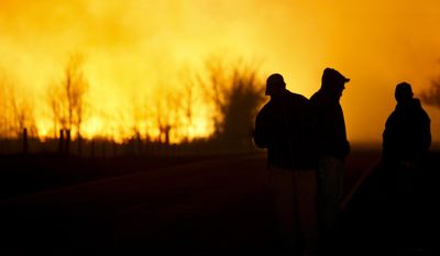 People are silhouetted against the orange glow of the fire as they watch a large grass fire burning out of control on Monday, March 6, 2017, in the northeast of Hutchinson, Kan. (Lindsey Bauman/The Hutchinson News via AP)