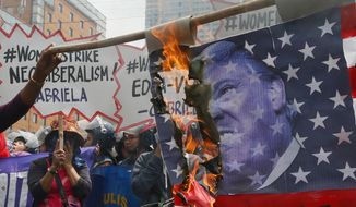 Women burn a mock American flag with the portrait of U.S. President Donald Trump during a rally at the U.S. Embassy to mark International Women's Day Wednesday, March 8, 2017 in Manila, Philippines. Women all over the world mark the women's day with rallies and protests to highlight the role of women in society. (AP Photo/Bullit Marquez)