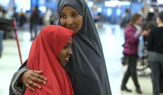 Halima Mohamed, embraces her daughter Muzamil Shalle, 14, not long after seeing her and her sister for the first time in seven years at John F. Kennedy International Airport in New York, Wednesday, March 8, 2017. The parents, who are from Somalia but have been living in Mechanicsburg, Pa., were originally scheduled to receive the children earlier this year, but the process was delayed due to a security check expiring as a result of delayed travel caused by the Jan. 27, 2017, White House travel ban executive order. (AP Photo/Craig Ruttle)