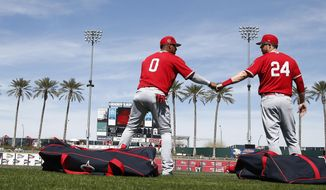 Los Angeles Angels' Yunel Escobar (0) and C.J. Cron (24) fist bump as the warm up prior to a spring training baseball game against the Cincinnati Reds Wednesday, March 8, 2017, in Goodyear, Ariz. (AP Photo/Ross D. Franklin)