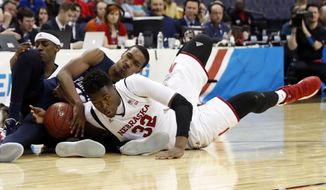 Penn State guard Tony Carr, back center, attempts to hold onto the loose ball as Nebraska center Jordy Tshimanga (32) reaches for it, during the first half of an NCAA college basketball game in the Big Ten Conference tournament, Wednesday, March 8, 2017, in Washington. (AP Photo/Alex Brandon)