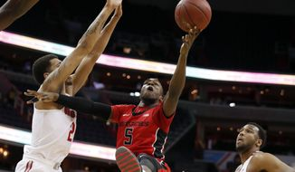 Rutgers guard Mike Williams (5) shoots between Ohio State forward Marc Loving, left, and Ohio State center Trevor Thompson (32) during the first half of an NCAA college basketball game in the Big Ten tournament, Wednesday, March 8, 2017, in Washington. (AP Photo/Alex Brandon)