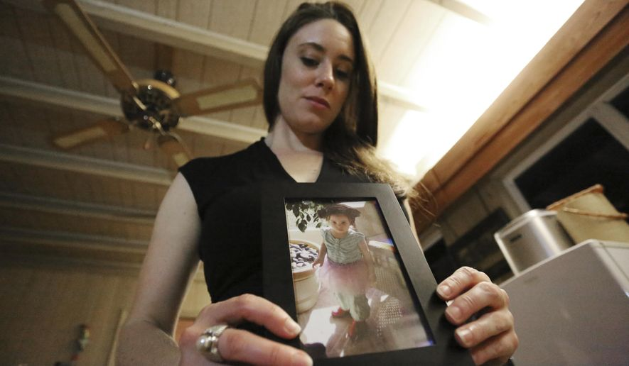In this Feb. 13, 2017 photo, Casey Anthony poses with a photo of her daughter Caylee during an interview in her West Palm Beach, Fla., home. Anthony, 30, opens up for the first time on-the-record about the death of her daughter in 2008. (AP Photo/Joshua Replogle)
