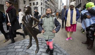 """Shriya Gupta of Cherokee, N.C. strikes a pose with a statue titled """"Fearless Girl"""", Wednesday, March 8, 2017, in New York. The statue was installed by an investment firm in honor of International Women's Day.   (AP Photo/Mark Lennihan)"""
