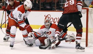 Carolina Hurricanes goalie Eddie Lack, center, blocks the shot of Arizona Coyotes' Brendan Perlini (29) as Hurricanes defenseman Matt Tennyson (26) defends during the second period of an NHL hockey game, Sunday, March 5, 2017, in Glendale, Ariz. (AP Photo/Ralph Freso)