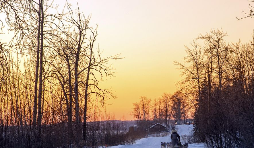 In this image taken Tuesday, March 7, 2017, and provided by the Iditarod Trail Committee, the sun sets as veteran musher Nicolas Petit makes his way into Tanana, Alaska, the third checkpoint of the Iditarod Trail Sled Dog Race. (Mike Kenney/Iditarod Trail Committee via AP)