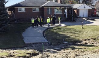 Michigan State Police and Macomb County officials check one of three houses Wednesday, March 8, 2017, in Fraser, Mich., that had to be condemned after a broken sewer line caused a football field-sized sinkhole on Christmas Eve. It likely will take until Thanksgiving to repair damage from a broken sewer line that caused the sinkhole on Christmas Eve north of Detroit, a public works official said Wednesday.  (AP Photo/Roger Schneider)