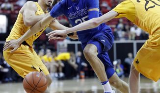 Air Force's Hayden Graham drives to the basket as Wyoming's Cody Kelley, left, and Hayden Dalton defend during the second half of an NCAA college basketball game in the Mountain West Conference tournament Wednesday, March 8, 2017, in Las Vegas. Air Force defeated Wyoming 83-68. (AP Photo/Isaac Brekken)