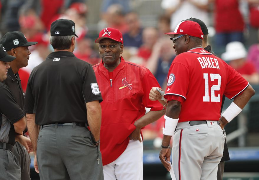 Former St. Louis Cardinals pitcher and Baseball Hall of Fame member Bob Gibson, center, exchanges lineup cards with Washington Nationals manager Dusty Baker (12) before a spring training baseball game Wednesday, March 8, 2017, in Jupiter, Fla. (AP Photo/John Bazemore)