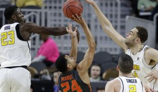 California's Kameron Rooks, right, blocks a shot by Oregon State's Kendal Manuel (24) during the first half of an NCAA college basketball game in the first round of the Pac-12 men's tournament Wednesday, March 8, 2017, in Las Vegas. California's Jabari Bird is on the left. (AP Photo/John Locher)
