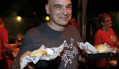 FILE - In this Feb. 24, 2012 file photo, Michael Symon holds his Porky Burgers during the Burger Bash at the Food Network South Beach Wine & Food Festival in Miami Beach, Fla. Celebrity Chef and cookbook author Symon plans to open a restaurant at Cleveland Hopkins International Airport this spring. The Bar Symon restaurant planned for the airport is expected to open in April 2017.  (AP photo/Jeffrey M. Boan, File)