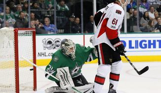 Dallas Stars' Antti Niemi (31) of Finland peers around Ottawa Senators' Mark Stone (61) as a shot by Viktor Stalberg, not shown, enters the net for a score in the second period of an NHL hockey game in Dallas, Wednesday, March 8, 2017. (AP Photo/Tony Gutierrez)