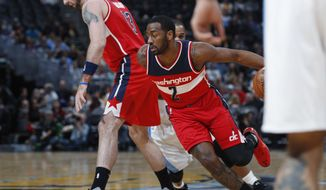 Washington Wizards guard John Wall slips past center Marcin Gortat, front left, who sets a screen on Denver Nuggets guard Jameer Nelson during the first half of an NBA basketball game Wednesday, March 8, 2017, in Denver. (AP Photo/David Zalubowski)