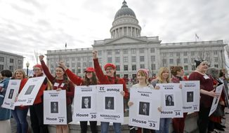 Women dressed in red and holding signs with photos of their local lawmakers are gathered at the Utah state capitol for a Day Without a Woman protest to remind legislators they're closely watching how they handle women's issues Wednesday, March 8, 2017, in Salt Lake City. (AP Photo/Rick Bowmer)