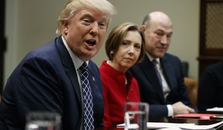 President Donald Trump, accompanied by Cape Cod Five Cents Savings Bank CEO Dorothy Savarese, center, and National Economic Council Director  Gary Cohn, speaks during a meeting with leaders from small community banks, Thursday, March 9, 2017, in the Roosevelt Room of the White House in Washington. (AP Photo/Evan Vucci)