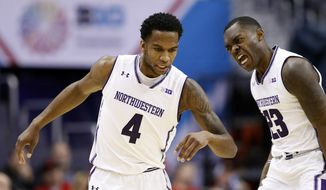 Northwestern forward Vic Law (4) and guard Jordan Ash (23) celebrate after a play during the first half of an NCAA college basketball game against Rutgers in the Big Ten tournament, Thursday, March 9, 2017, in Washington. (AP Photo/Alex Brandon)
