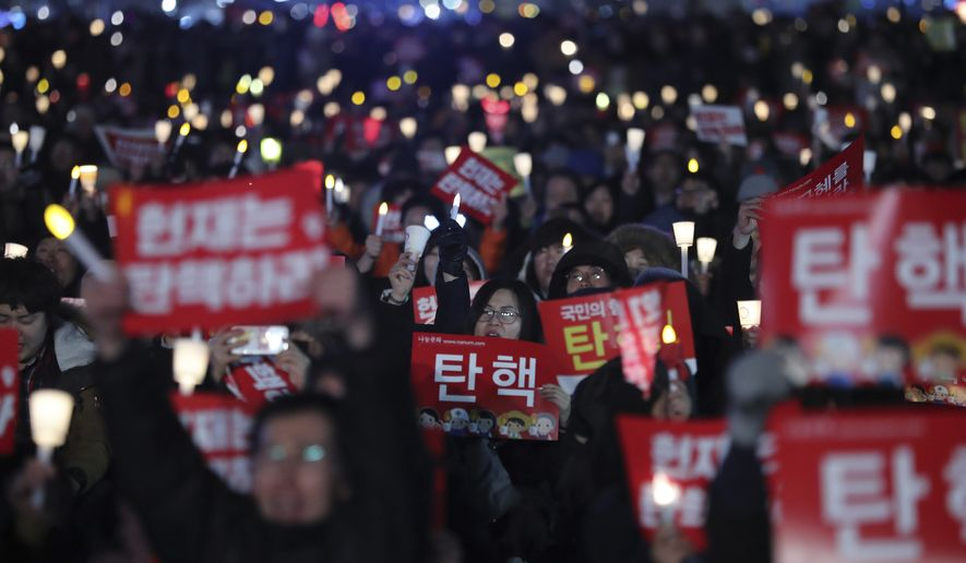 """Protesters shout slogans during a rally calling for the impeachment of President Park Geun-hye in Seoul, South Korea, Thursday, March 9, 2017. South Korean President Park Geun-hye finds out Friday whether a court will remove her from office over a corruption scandal or allow her to complete her term. The letters read """"Impeachment."""" (AP Photo/Lee Jin-man)"""