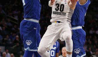 Seton Hall forward Angel Delgado, left, and Seton Hall guard Khadeen Carrington, right, defend Marquette guard Andrew Rowsey, center,  during the first half a Big East quarterfinal college basketball game at Madison Square Garden, Thursday, March 9, 2017, in New York.  (AP Photo/Kathy Willens)
