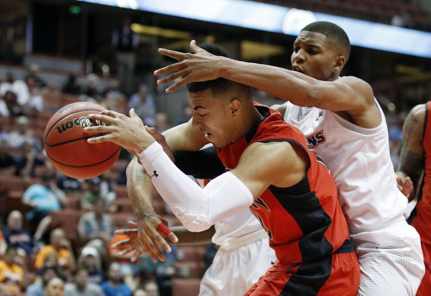 Cal State Northridge's Kendall Smith, center, and Cal State Fullerton's Tre Coggins vie for a loose ball during the first half of an NCAA college basketball game at the Big West men's tournament Thursday, March 9, 2017, in Anaheim, Calif. (AP Photo/Jae C. Hong)