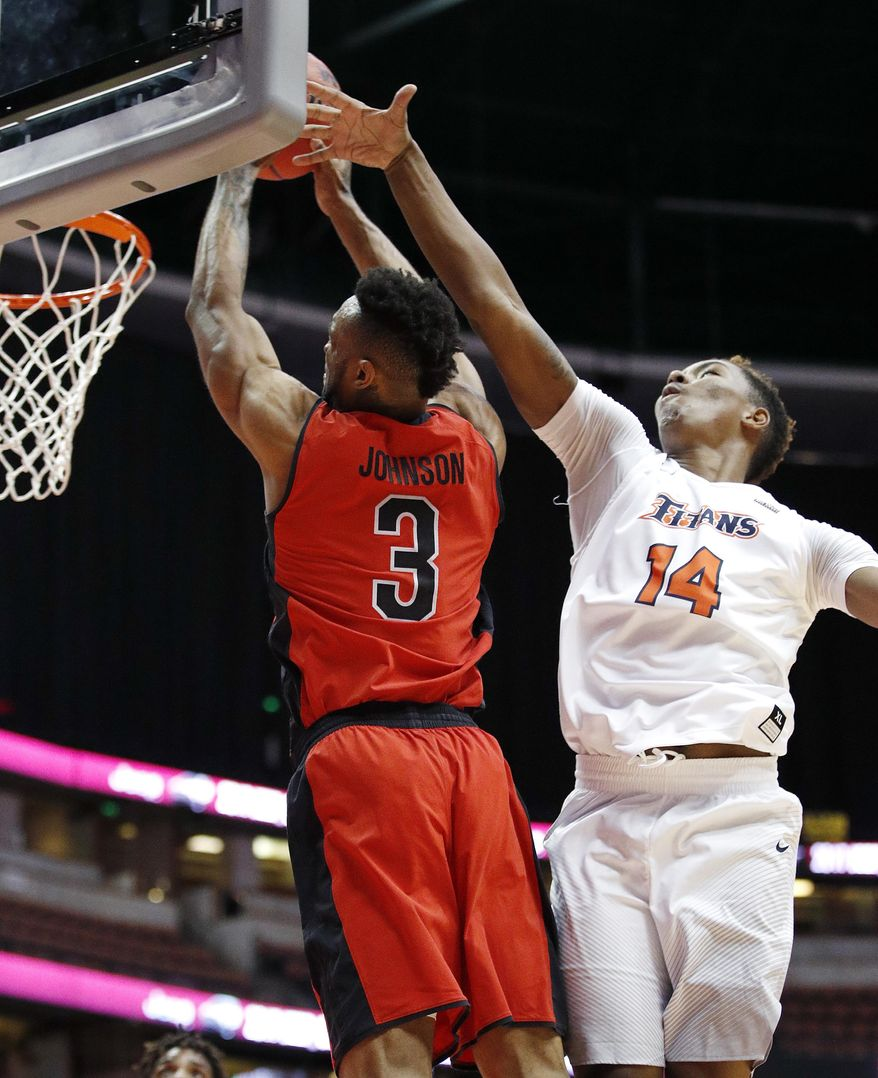 Cal State Northridge's Darin Johnson, left, goes up for a dunk past Cal State Fullerton's Khalil Ahmad during the first half of an NCAA college basketball game at the Big West conference men's tournament on Thursday, March 9, 2017, in Anaheim, Calif. (AP Photo/Jae C. Hong)