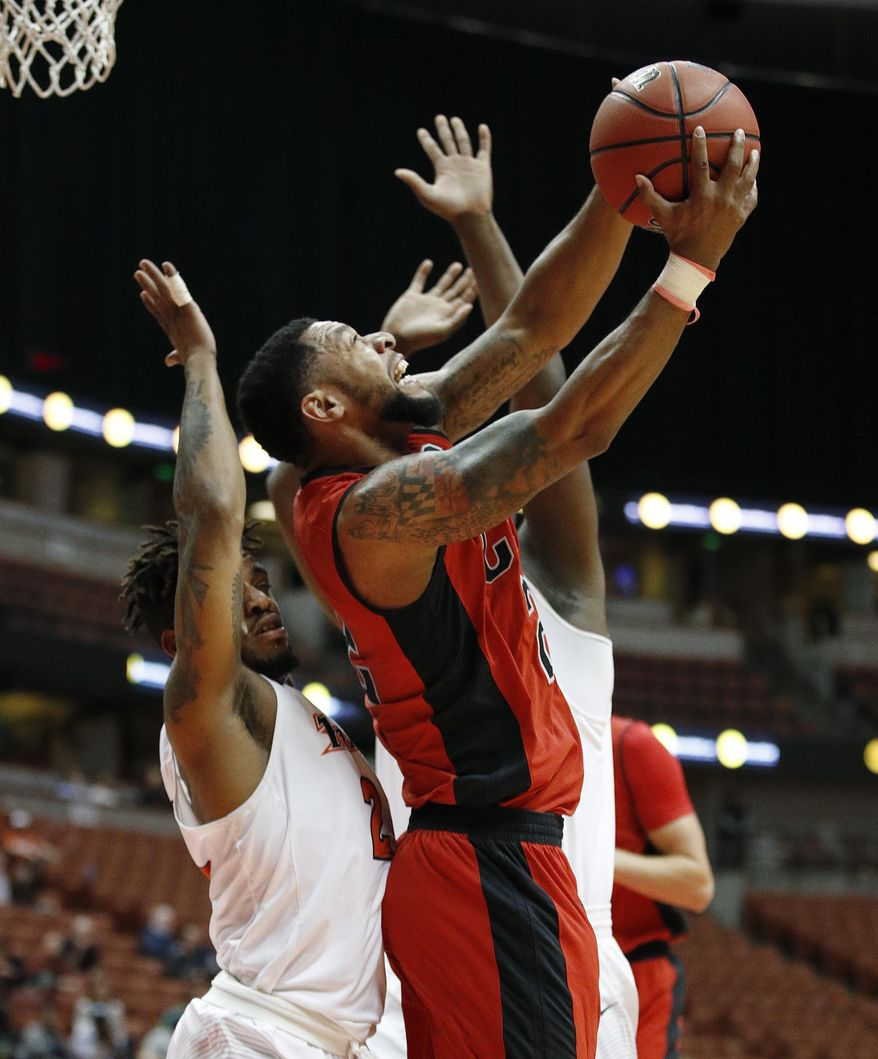 Cal State Northridge's Aaron Parks, right, looks to shoot under defense by Cal State Fullerton's Lionheart Leslie during the first half of an NCAA college basketball game at the Big West conference men's tournament on Thursday, March 9, 2017, in Anaheim, Calif. (AP Photo/Jae C. Hong)