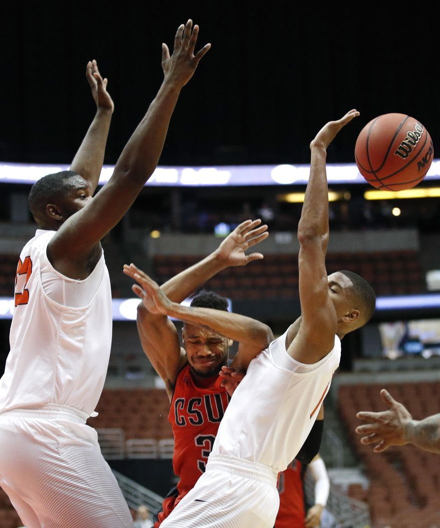 Cal State Northridge's Darin Johnson, center, is double-teamed by Cal State Fullerton's Tre Coggins, right, and Richard Peters during the first half of an NCAA college basketball game at the Big West conference men's tournament on Thursday, March 9, 2017, in Anaheim, Calif. (AP Photo/Jae C. Hong)