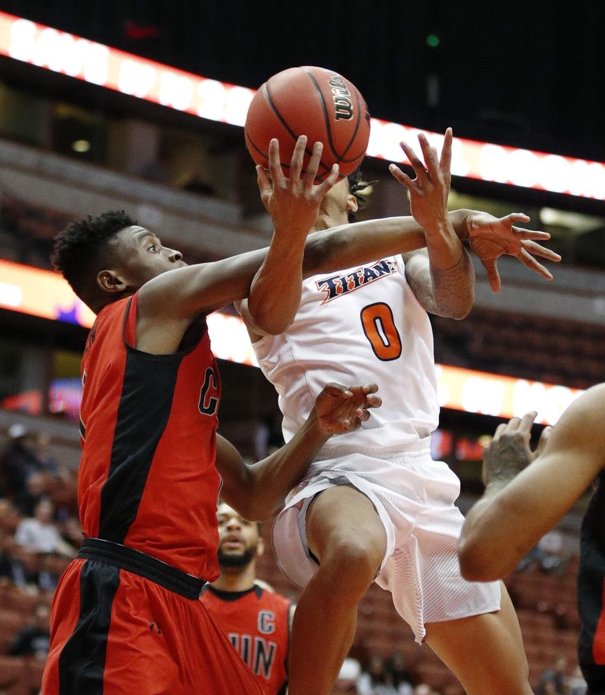 Cal State Northridge's Micheal Warren, left, fouls Cal State Fullerton's Kyle Allman during the second half of an NCAA college basketball game at the Big West conference men's tournament on Thursday, March 9, 2017, in Anaheim, Calif. Cal State Fullerton won 81-68. (AP Photo/Jae C. Hong)