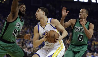 Golden State Warriors' Klay Thompson, center, looks for a shot between Boston Celtics' Amir Johnson, left, and Avery Bradley during the first half of an NBA basketball game Wednesday, March 8, 2017, in Oakland, Calif. (AP Photo/Ben Margot)