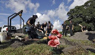 In this Sept. 15, 2016 photo, Dr. Erin Kimmerle, center, works with investigators as they examine the remains of an unidentified 1985 female murder victim after the body was exhumed from a unmarked grave in Tampa, Fla. Kimmerle knows locating the killer is a long shot. But she feels maybe if she is detailed enough and throws enough science at the case, she can identify the body and find relatives. (AP Photo/Chris O'Meara)