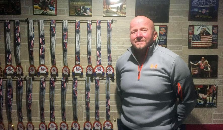 ADVANCE FOR USE SUNDAY, MARCH 12, 2017 AND THEREAFTER - In this Jan. 30,  2017 photo, personal trainer Duane Burlingame stands in his home gym in Freeport, Ill., next to just a few of the medals he's won in weightlifting competitions. Burlingame, 59, has competed in drug-tested weightlifting events all over the United States since 1998. Aside from his 96 world titles, he's captured 28 world cups, 56 national titles and 72 regional titles. In the process, he's also set 139 national and 152 state records. (Derrick Mason/The Journal-Standard, via AP)