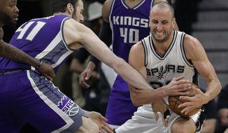 Sacramento Kings center Kosta Koufos (41) tries to strip the ball from San Antonio Spurs guard Manu Ginobili (20) during the second half of an NBA basketball game, Wednesday, March 8, 2017, in San Antonio. The Spurs won 114-104. (AP Photo/Eric Gay)