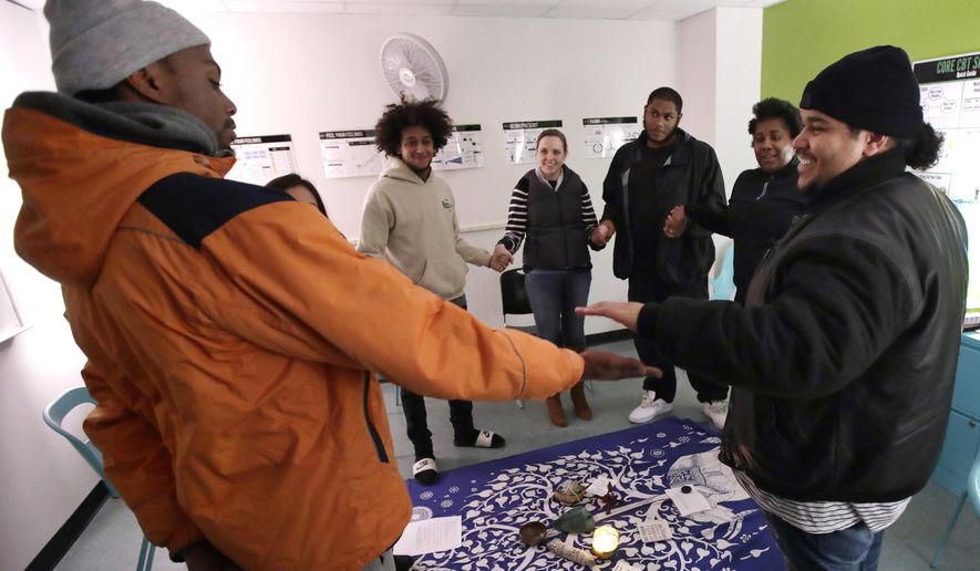 """ADVANCE FOR USE MONDAY, MARCH 13, 2017 AND THEREAFTER-Young men participating in the Roca Inc. prison alternative program join hands during a peacemaking circle session in Boston, Thursday, Jan. 12, 2017. With its motto """"Less jail, more future,"""" Roca aims not just to save young people from wasting their lives but to save taxpayers from wasting their money. According to Roca, the annual cost of incarceration in Massachusetts is about $53,500 per person, while Roca's program costs about $26,000 per person for four years. (AP Photo/Charles Krupa)"""