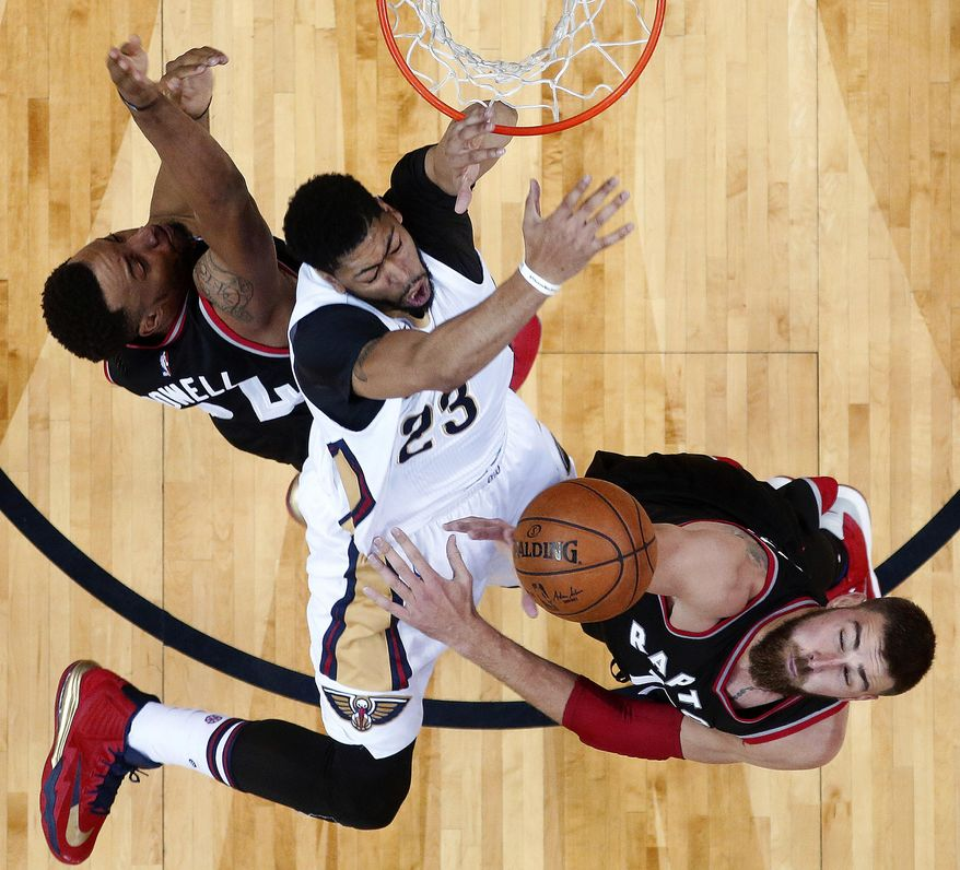 New Orleans Pelicans forward Anthony Davis (23) hits his wrist on the rim as he is fouled under the basket between Toronto Raptors guard Norman Powell, left, and center Jonas Valanciunas, right, during the first half of an NBA basketball game in New Orleans, Wednesday, March 8, 2017. Davis was injured on the play and left the game with a wrist contusion. The Raptors won 94-87. (AP Photo/Gerald Herbert)