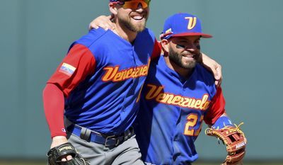 Venezuela center fielder Ender Inciarte, left, is congratulated by second baseman Jose Altuve after Inciarte made a diving catch for an out on Kansas City Royals' Raul Mondesi to end the fourth inning during a spring training baseball game, Wednesday, March 8, 2017, in Surprise, Ariz. (John Sleezer/The Kansas City Star via AP)