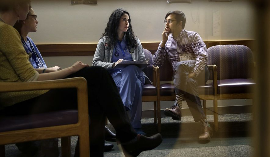 """In this Monday, Feb. 27, 2017, photo, Cambridge Hospital first-year residents Samantha Harrington, center, and Vikas Gampa, right, talk during """"sign-out"""" at the hospital in Cambridge, Mass. That's when the rookie doctors exchange information about their patients during shift change. Effective this summer, rookie doctors can work up to 24 hours straight under new extended limits. A Chicago-based group that establishes work standards for U.S. medical school graduates has eliminated a 16-hour cap for first-year residents. (AP Photo/Steven Senne)"""