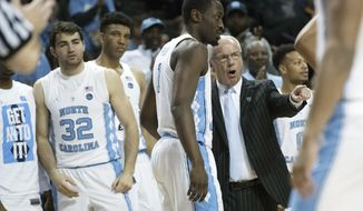 North Carolina head coach Roy Williams, right, gives forward Theo Pinson (1) instruction during the second half of an NCAA college basketball game against the Miami in the Atlantic Coast Conference tournament, Thursday, March 9, 2017, in New York. North Carolina won 78-53. (AP Photo/Mary Altaffer)