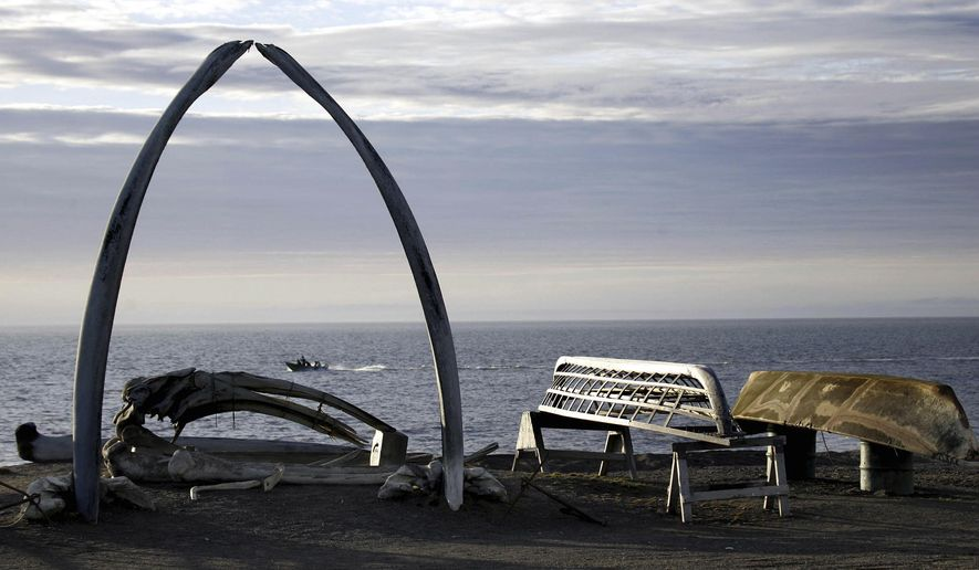 FILE - In this Aug. 12, 2005, file photo, a boat drives past a skin boat display near whale bones and an arch made of a whale jaw on the beach in a town that was known as Barrow, Alaska. A judge in Alaska has dealt a legal blow to opponents of the new Inupiat Eskimo name approved by voters in the nation's northernmost town. Superior Court Judge Paul Roetman on Friday, March 10, 2017, denied a request to halt implementation of the transition from the old name of Barrow to Utqiagvik until a lawsuit filed by a local Alaska Native corporation is resolved. (AP Photo/Al Grillo, File)