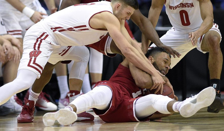 Wisconsin guard Zak Showalter, top, scrambles for the ball against Indiana guard James Blackmon Jr., bottom, during the first half of an NCAA college basketball game in the Big Ten tournament, Friday, March 10, 2017, in Washington. (AP Photo/Nick Wass)