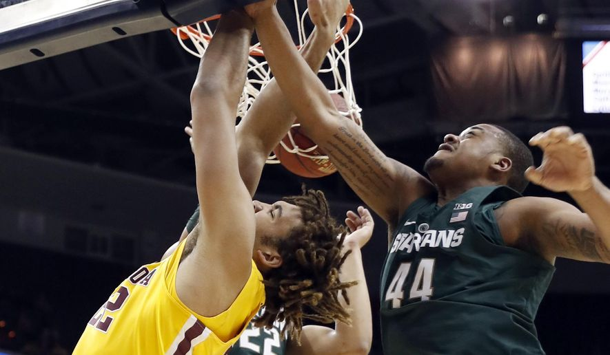 Minnesota center Reggie Lynch, left, dunks the ball past Michigan State guard Miles Bridges, back, and forward Nick Ward, right, during the first half of an NCAA college basketball game in the Big Ten tournament, Friday, March 10, 2017, in Washington. (AP Photo/Alex Brandon)