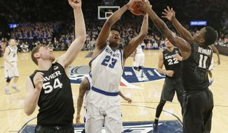 Creighton's Justin Patton (23) and Xavier's Malcolm Bernard (11) fight for the ball as Xavier's Sean O'Mara (54) gets caught in the net during the first half of an NCAA college basketball game during the Big East men's tournament Friday, March 10, 2017, in New York. (AP Photo/Frank Franklin II)