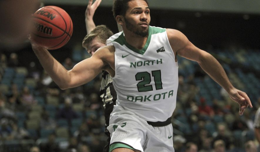 North Dakota guard Quinton Hooker (21) passes off under the basket against Idaho during the first half an NCAA college basketball game in the semifinals of the Big Sky tournament in Reno. Nev., Friday, March 10, 2017. (AP Photo/Lance Iversen)
