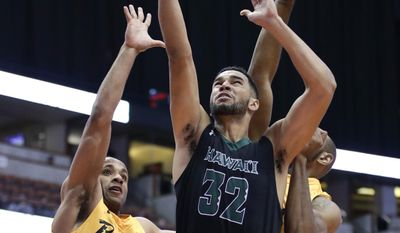 Hawaii's Noah Allen, center, goes up for a basket past Long Beach State's Evan Payne, left, and Roschon Prince during the first half of an NCAA college basketball game at the Big West men's tournament Thursday, March 9, 2017, in Anaheim, Calif. (AP Photo/Jae C. Hong)