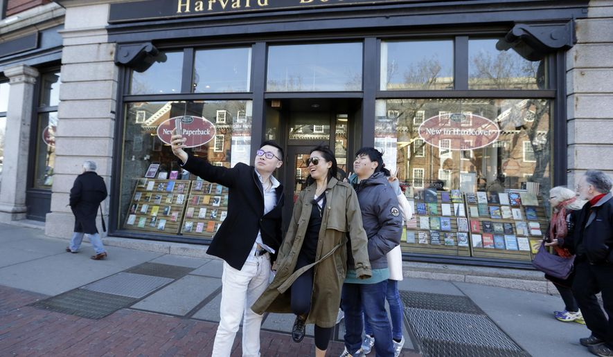 """Students pose for a selfie outside the Harvard Book Store, Thursday, March 9, 2017, in Cambridge, Mass. Readers have been flocking to classic works of dystopian fiction in the first months of Donald Trump's presidency. Novels depicting dysfunctional societies have shot to the top of best-seller lists in recent months, including George Orwell's """"1984"""" and Margaret Atwood's """"The Handmaid's Tale."""" Publishers credit Trump's election for sparking demand. (AP Photo/Elise Amendola)"""